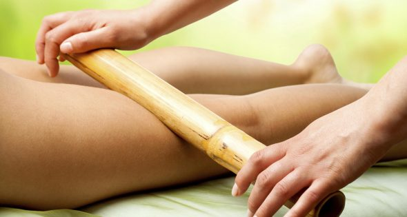 Bamboo massage on female legs by therapist