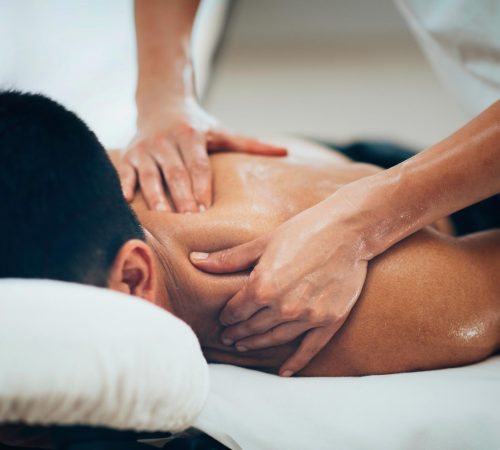 Sports massage on the man upper back